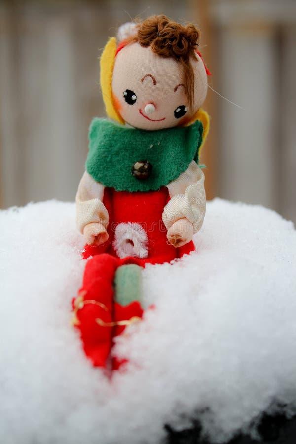 Boneca do duende do Natal que senta-se sobre a tração da neve com fundo distante atrás levemente fora de foco imagem de stock