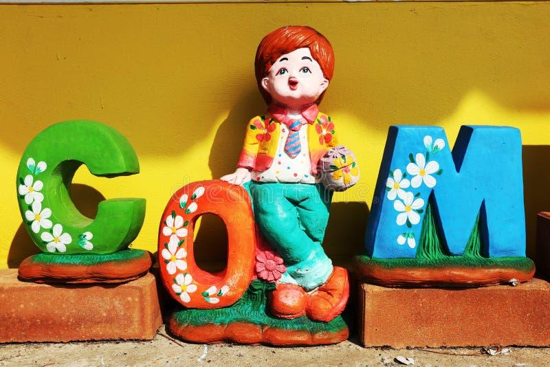 A boneca do menino moldou da argila que está ao lado da letra O de COM da palavra fotografia de stock