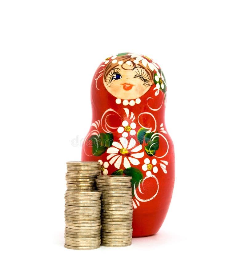 Boneca do russo e pilhas das moedas imagem de stock