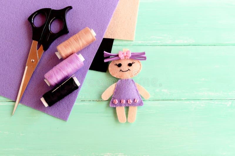 Boneca feita casa de feltro, tesouras, linha, agulha, partes lisas de feltro em um fundo de madeira claro com lugar vazio para o  imagens de stock