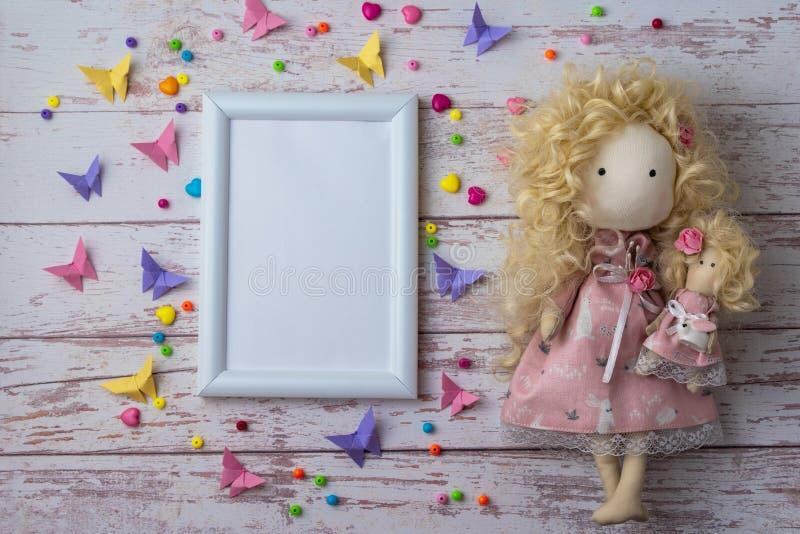 Boneca feito a mão da tela com grânulos coloridos, as borboletas de papel e quadro branco da foto fotos de stock royalty free