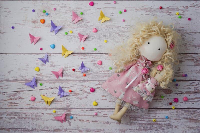 Boneca feito a mão da tela perto dos grânulos coloridos, borboletas de papel imagens de stock