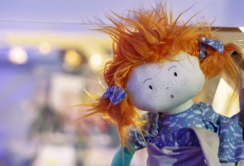 Boneca macia do brinquedo com cabelo vermelho e o vestido roxo fotos de stock