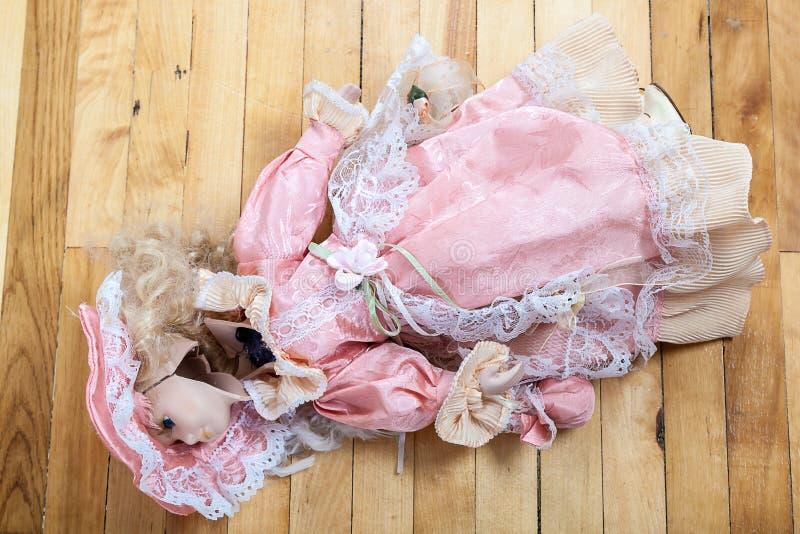 Boneca quebrada em um assoalho de madeira fotos de stock