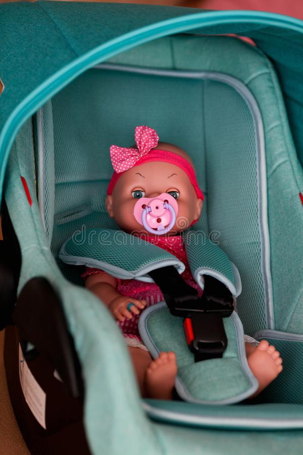 A boneca senta-se em uma cadeira do automóvel foto de stock royalty free