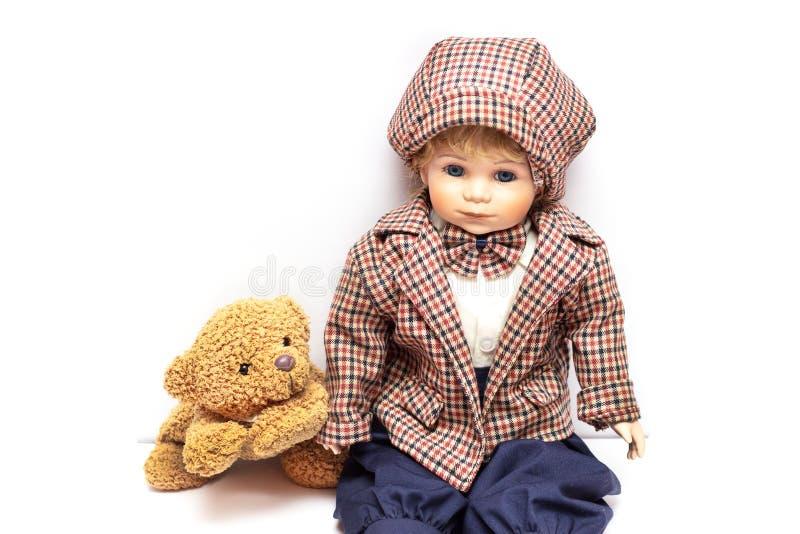 Boneca velha da porcelana no fundo branco, em bonecas cerâmicas e em um urso de peluche foto de stock royalty free