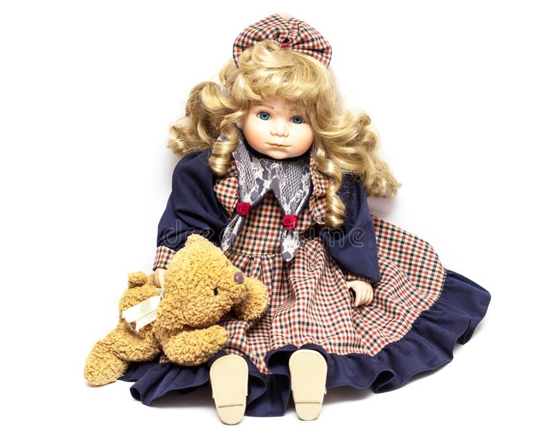 Boneca velha da porcelana no fundo branco, em bonecas cerâmicas e em um urso de peluche imagens de stock royalty free