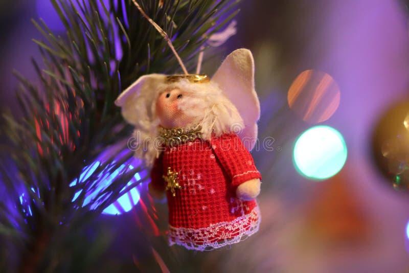 Boneca vermelha da árvore do ano novo do Natal com luzes de Natal imagens de stock royalty free