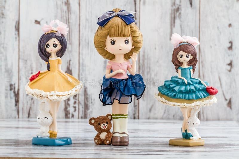 Bonecas bonitos decorativas no fundo de madeira branco foto de stock royalty free