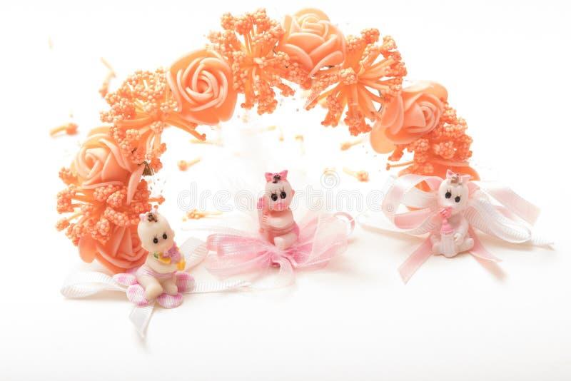 Bonecas bonitos que sentam-se na frente da festão w das flores artificiais fotos de stock royalty free