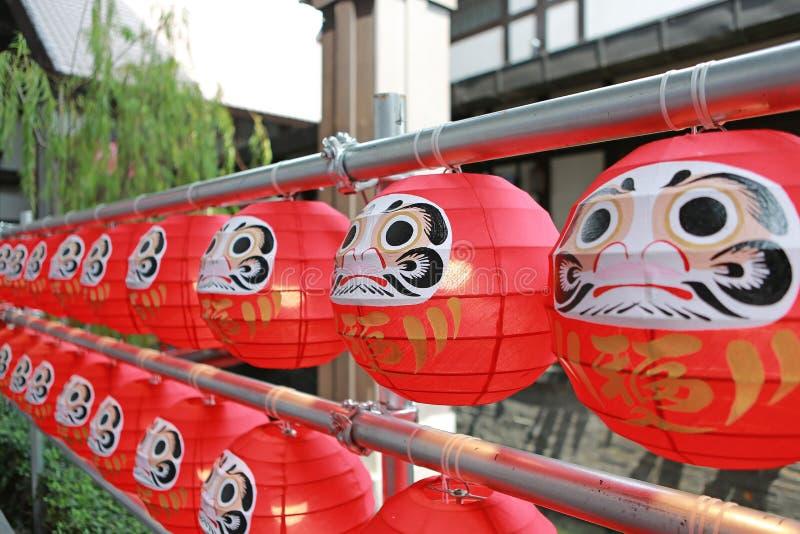 """Bonecas de Daruma As bonecas simbólicas afortunadas japonesas que penduram na fileira com tradução """"fortuna 'do texto foto de stock royalty free"""