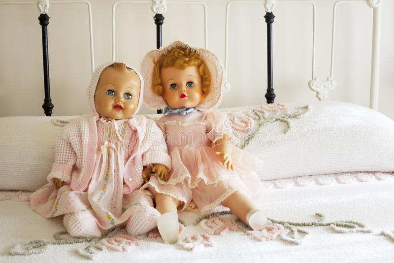Bonecas do vintage na colcha de Chanille na cama do ferro foto de stock