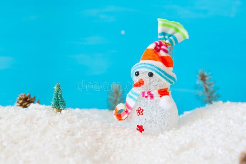 Boneco de neve bonito na neve sobre o fundo de madeira azul fotografia de stock