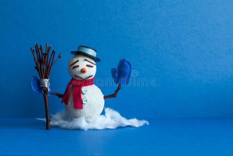 Boneco de neve cômico no fundo azul Caráter tradicional do boneco de neve do feriado de inverno com mitenes chapéu negro e vassou fotografia de stock