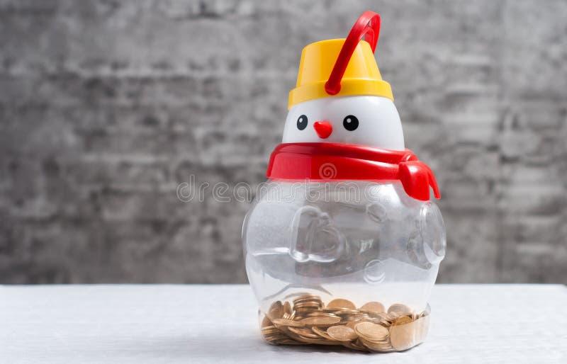 Boneco de neve com moedas, piggybank transparente, foto de stock