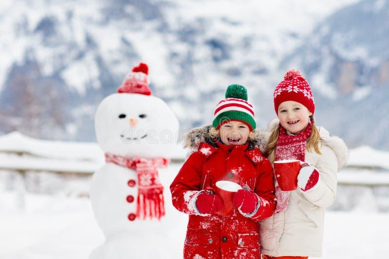 Boneco de neve da construção da criança As crianças constroem o homem da neve fotografia de stock