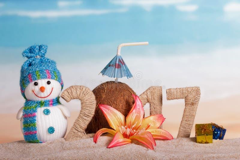 Boneco de neve do Natal, coco e inscrição 2017 na areia, decorada com flor, presentes foto de stock royalty free