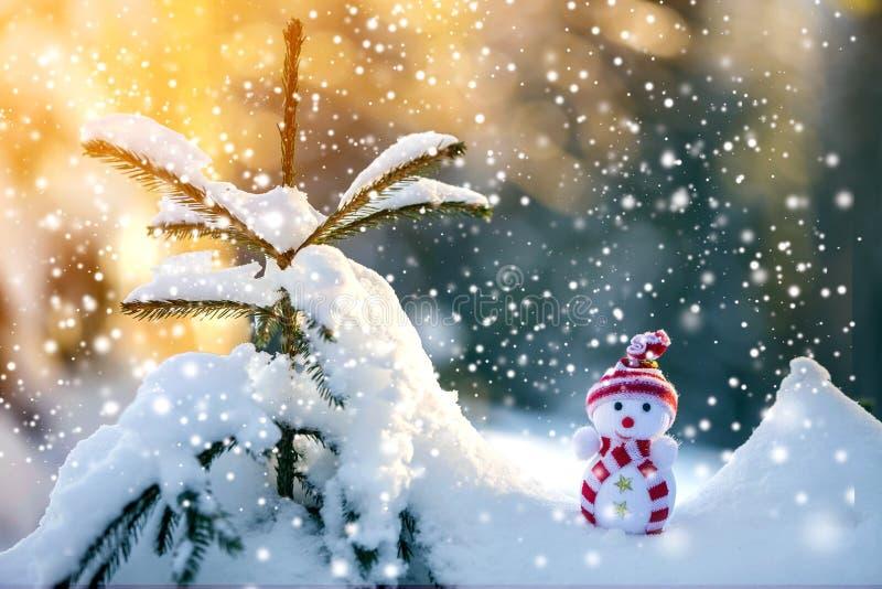 Boneco de neve engraçado pequeno do bebê do brinquedo no chapéu e no lenço feitos malha no sn profundo fotografia de stock royalty free