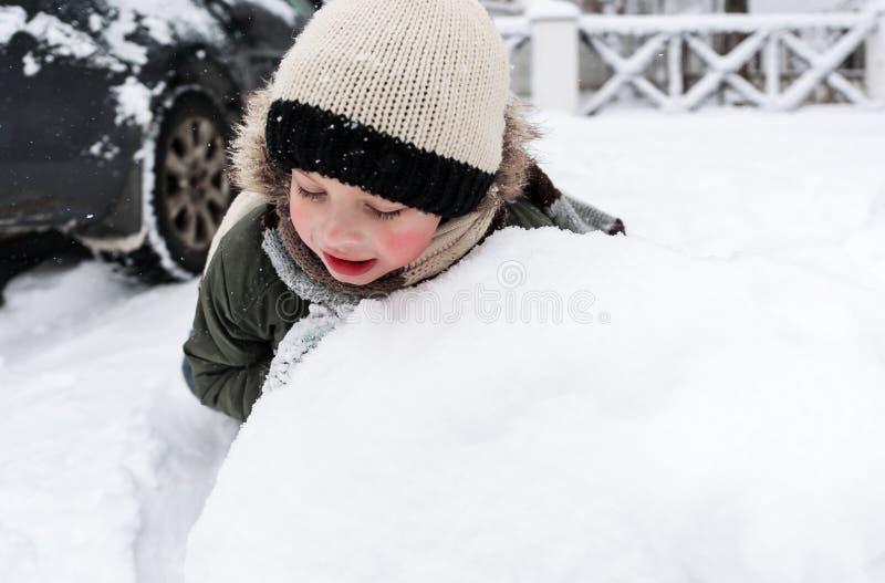 Boneco de neve feliz da construção da criança bonita no jardim, tempo de inverno fotos de stock royalty free