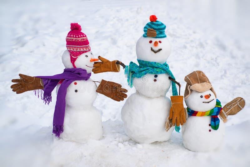 Boneco de neve pequeno bonito da família exterior Família feliz do boneco de neve em ramos cobertos de neve de um abeto do fundo  fotos de stock royalty free