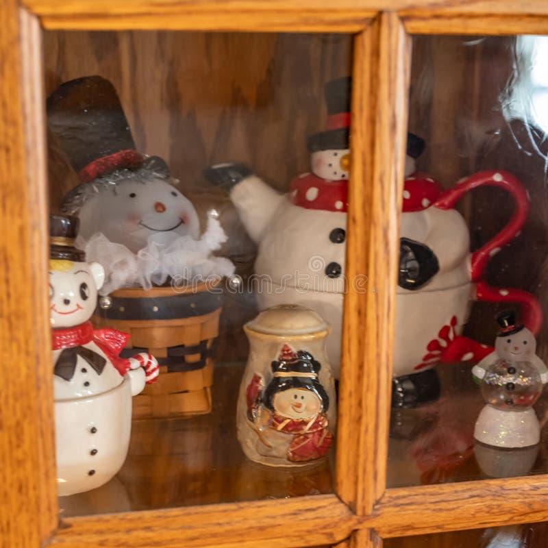 Bonecos de neve cerâmicos em uma prateleira para dentro de um armário imagem de stock