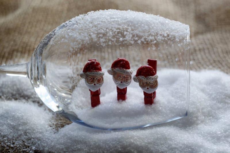 Bonecos de neve do Natal em pregadores de roupa, dentro de um cálice de vidro fotos de stock royalty free