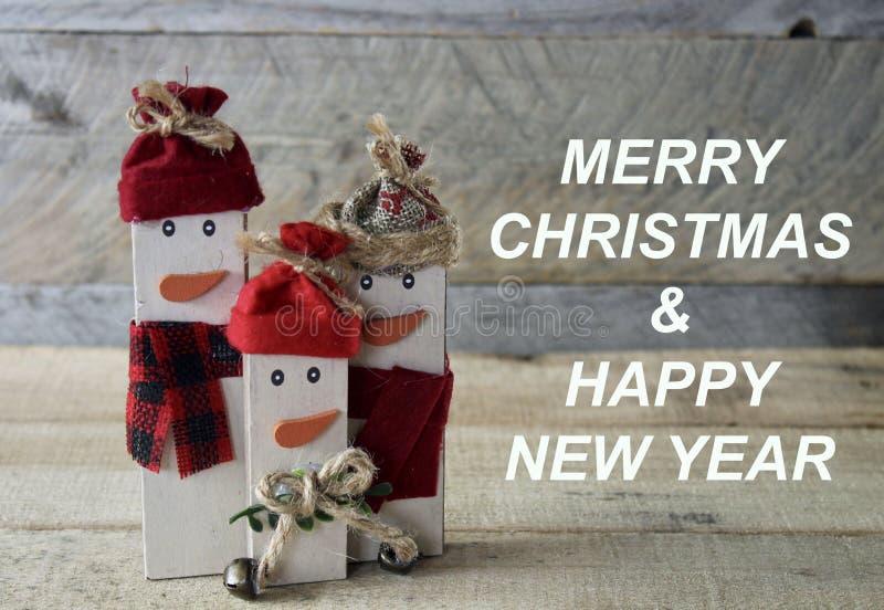 Bonecos de neve em um fundo de madeira com mensagem do Feliz Natal imagem de stock
