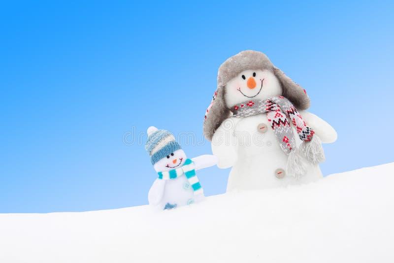 Bonecos de neve felizes família ou amigos do inverno contra o céu azul imagens de stock