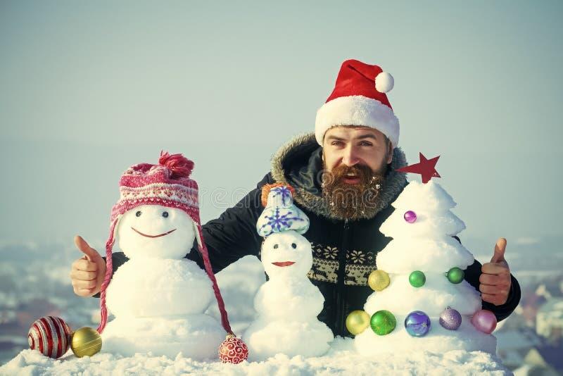 Bonecos de neve nos chapéus e árvore do xmas da neve no céu azul imagem de stock