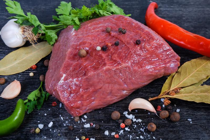 Boneless piece of fresh uncooked beef among spices close-up royalty free stock images