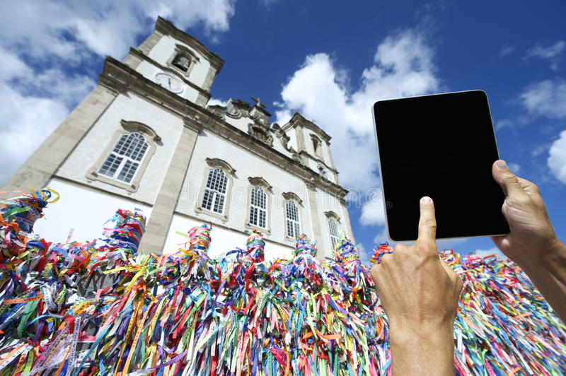 Bonfim Salvador Bahia Brazil Digital Tablet Computer. Finger of traveling tourist touching digital tablet computer at wall of Brazilian wish ribbons at Bonfim stock photos