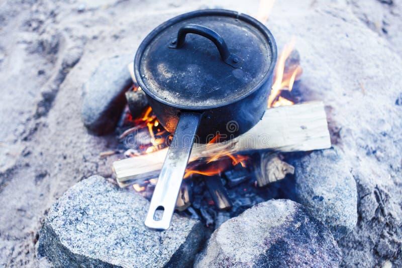 Bonfire bowler sur le sable sur la plage à la randonnée d'automne, concept de tourisme personne image stock