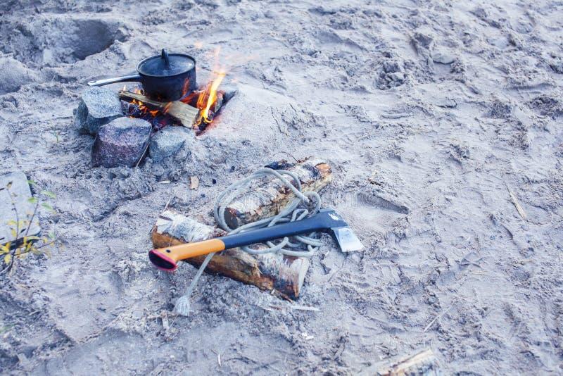 Bonfire bowler sur le sable sur la plage à la randonnée d'automne, concept de tourisme personne images stock