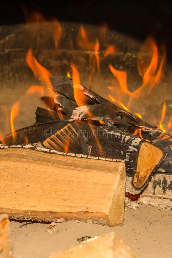 Bonfire brightly orange flame large logs burned covered with ash on sand close-up design base picnic on the ocean shore royalty free stock image