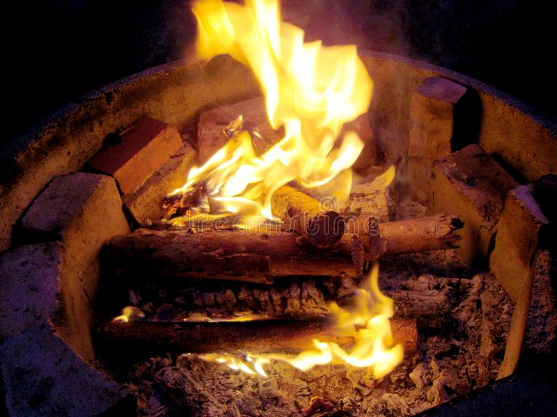 Bonfire is burning in nature. Smoldering firewood, glowing logs, closeup. Campfire flaming soft glowing flame stock image