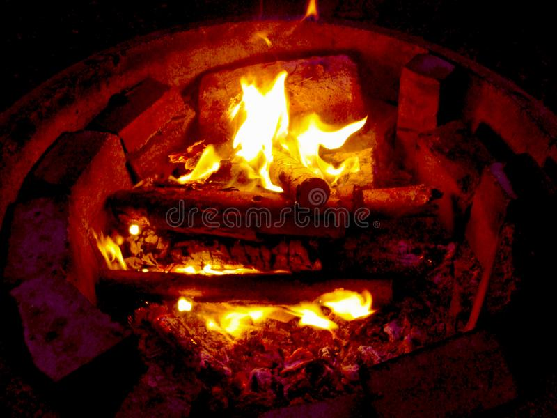 Bonfire is burning in nature. Smoldering firewood, glowing logs, closeup. Campfire flaming soft glowing flame royalty free stock photography