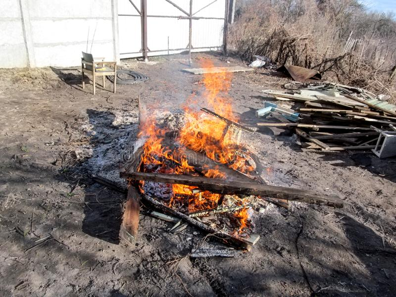 Bonfire from construction waste, burning wooden boards and other garbage. Environmental protection concept, fire burns remnants of royalty free stock photos
