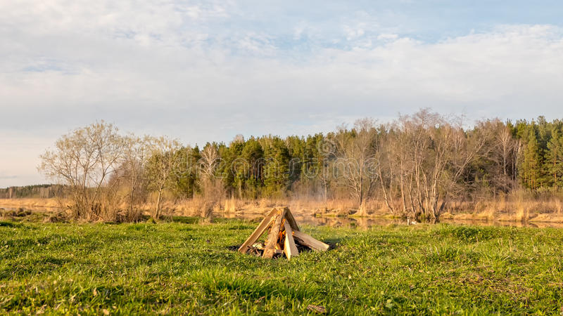 A bonfire in the field near the river stock image