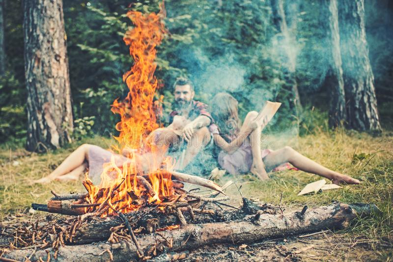 Bonfire flame with sparks and people on background. Fire burn in camp. Friends relax in smoke of campfire. Camping royalty free stock image