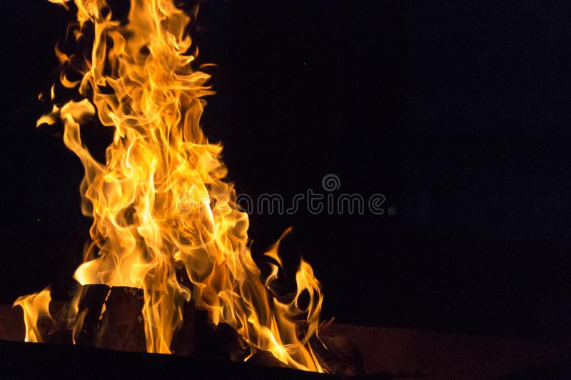 Bonfire illuminating the night. Devilish flame. The fire of hell. Background from dancing tongues of fire. Fire hazard. Fire safety. Passionate love. Bask around royalty free stock images