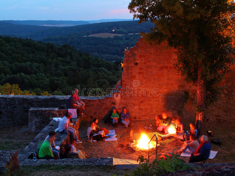Campfire summer night in castle ruin by twilight stock image