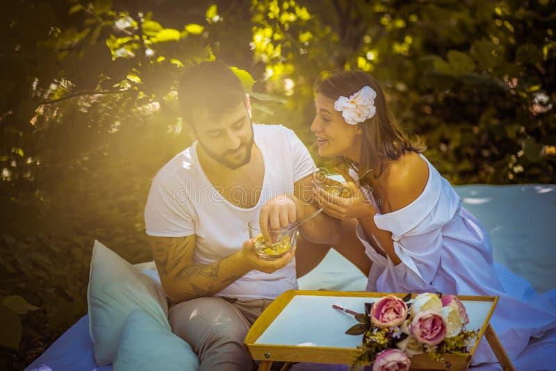 Bonheur pur Les couples dans l'amour à la nature prennent le petit déjeuner photos stock