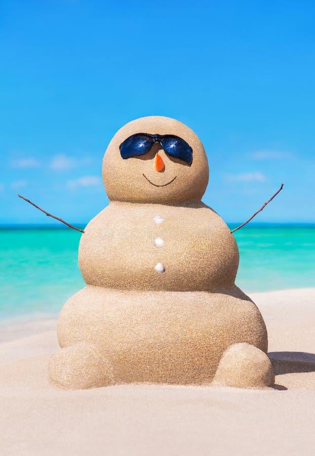 Bonhomme de neige arénacé drôle dans des lunettes de soleil à la plage ensoleillée tropicale d'océan images libres de droits