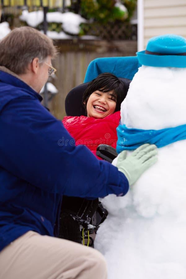 Bonhomme de neige de bâtiment de père pendant l'hiver avec le fils handicapé dans le fauteuil roulant photos libres de droits