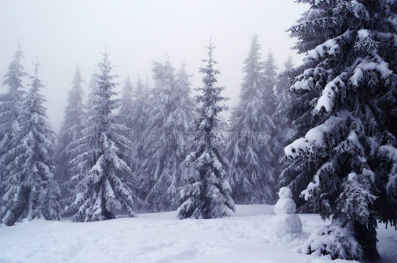 Bonhomme de neige dans la forêt parmi les arbres dans la neige photographie stock