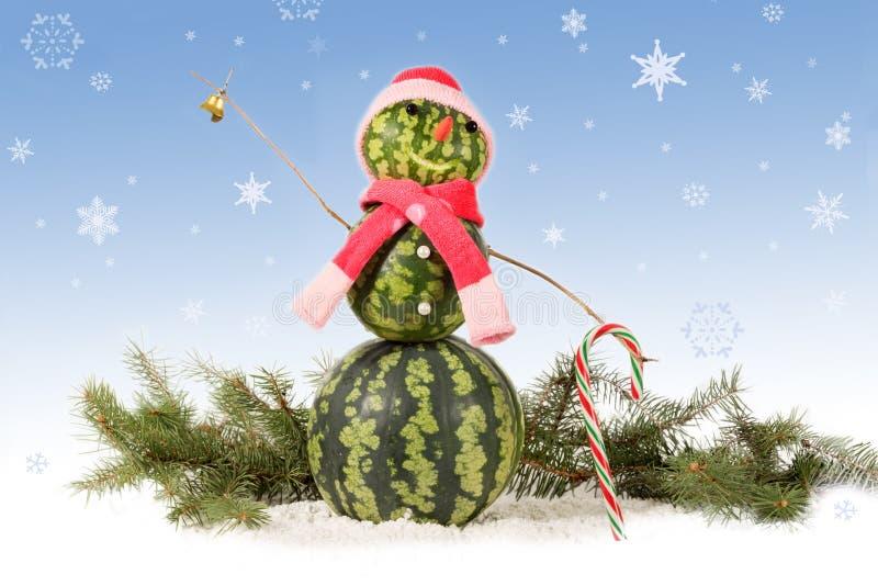 bonhomme de neige de pastèque dans le chapeau et l'écharpe rouges avec la canne de sucrerie sur le fond bleu et les flocons de ne images libres de droits