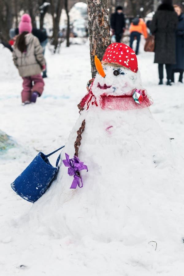 Bonhomme de neige drôle fait en neige tombée en parc d'hiver photos libres de droits