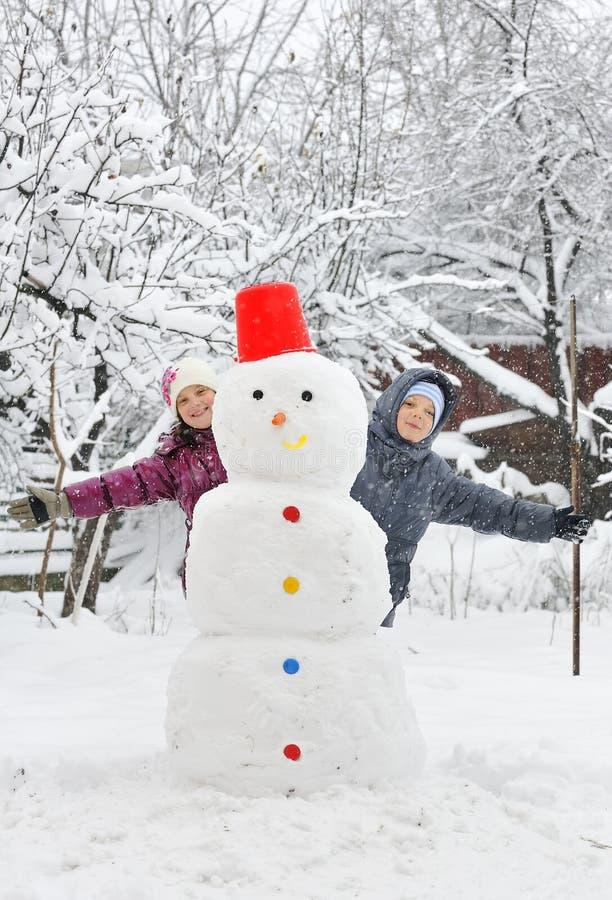 Bonhomme de neige et gosses photographie stock