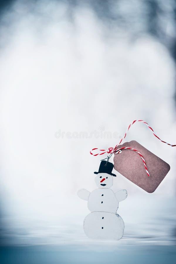 Bonhomme de neige heureux avec le chapeau noir, moquerie d'étiquette haute et ruban au fond neigeux de jour d'hiver Vacances d'hi photos libres de droits