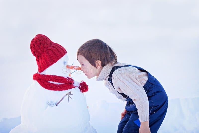 Bonhomme de neige heureux de bâtiment de bel enfant dans le jardin, hiver, nez t photographie stock libre de droits
